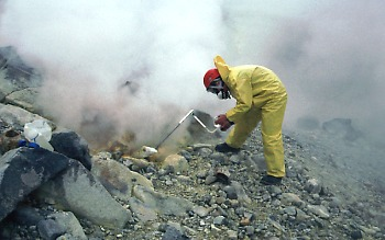 Scientist collecting gas sample from a fumarole on Mageik volcano Alaska