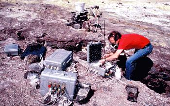 Scientist working on continuous gas monitoring equipment, Kilauea Volcano, Hawai`i