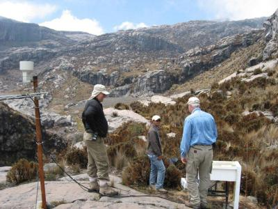 USGS and INGEOMINAS colleagues at an lahar-detection (Acoustic Flow Monitor or AFM) station on the west flank of Nevado del Ruiz, Colombia. View is up the glacial valley toward the summit area. (Click image to view full size.)