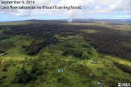 Lava flow (June 27) advancing northeast across ground surface after exiting ground crack system along KILAUEA's East Rift Zone, PUUOO, HAWAII. Smoke from burning trees, Kahoe Homesteads in foreground.