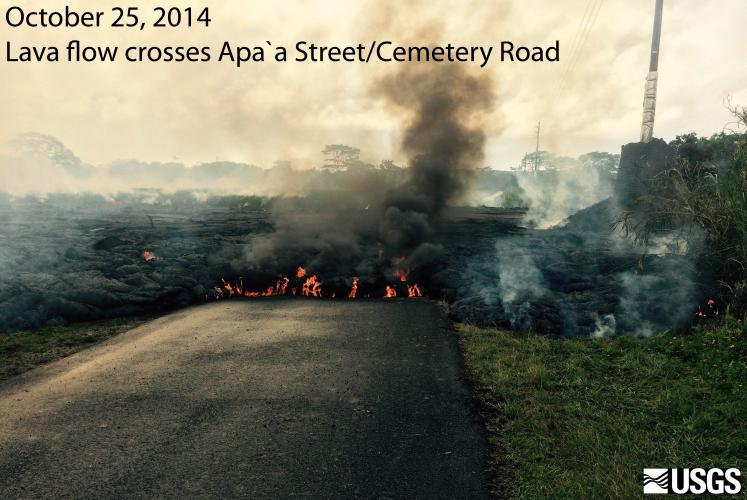 KILAUEA's June 27th lava flow crosses APAA road west of PAHOA Village, HAWAII. Dark smoke is from burning asphalt. Telephone pole upper right is wrapped in insulation then a barrier of cinder.