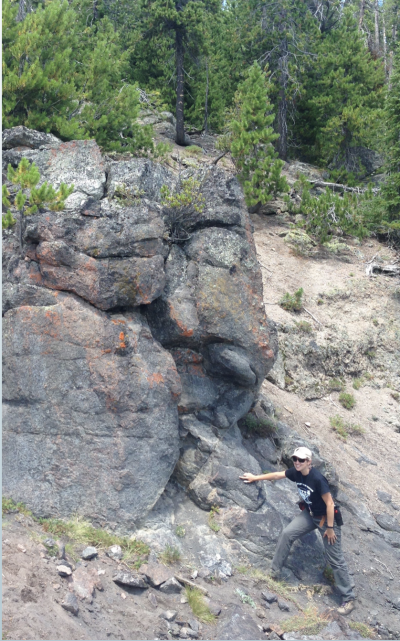 Christy Till, a scientist at Arizona State University points to one of the crystal black box recorders in the Scaup Lake lava flow, which erupted at Yellowstone around 256,000 years ago.  (Click image to view full size.)