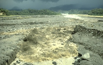 Lahar rushes down a confined river channel, Guatamala